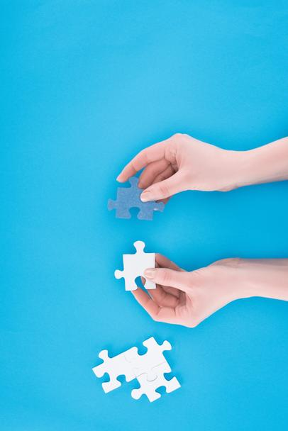 cropped image of businesswoman assembling blue and white puzzles isolated on blue, business concept - Photo, Image