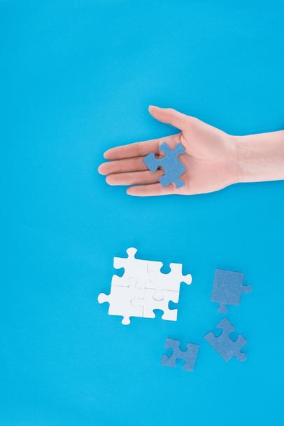 cropped image of businesswoman assembling puzzles and holding one piece on hand isolated on blue, business concept - Photo, Image