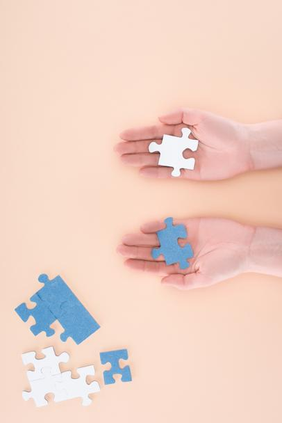 cropped image of businesswoman holding blue and white puzzles in hands isolated on beige, business concept - Photo, Image