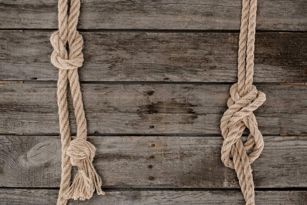 flat lay with marine ropes with knots on grunge wooden tabletop - Photo, Image