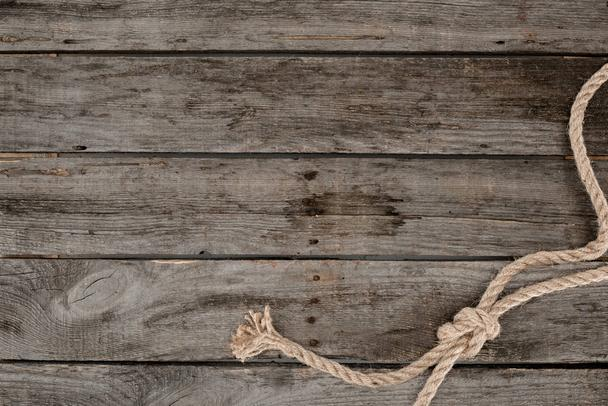 top view of nautical rope with knot on grunge wooden surface - Photo, Image