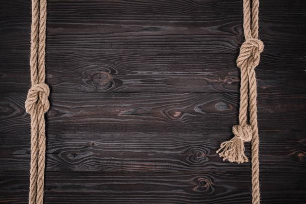 top view of arrangement of brown nautical ropes with knots on dark wooden tabletop - Photo, Image