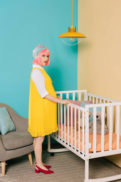 retro styled pregnant pin up woman with pink hair standing near baby bed - Photo, Image