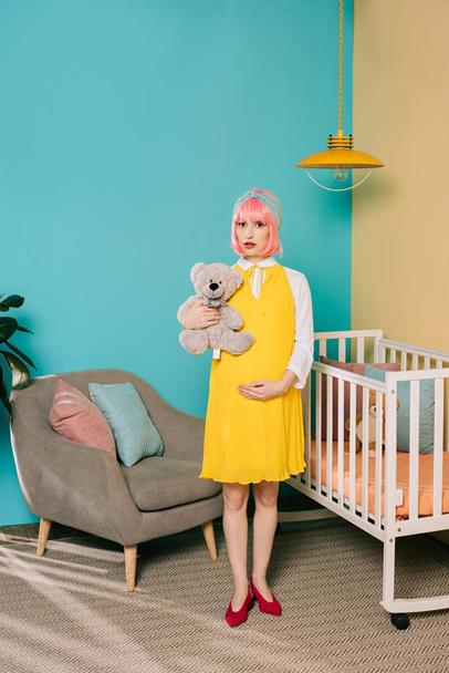 retro styled pregnant pin up woman with pink hair standing with teddy bear in child room - Photo, Image