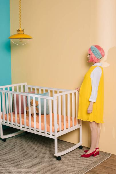 side view of retro styled pregnant pin up woman with pink hair standing near baby cot in child room - Photo, Image