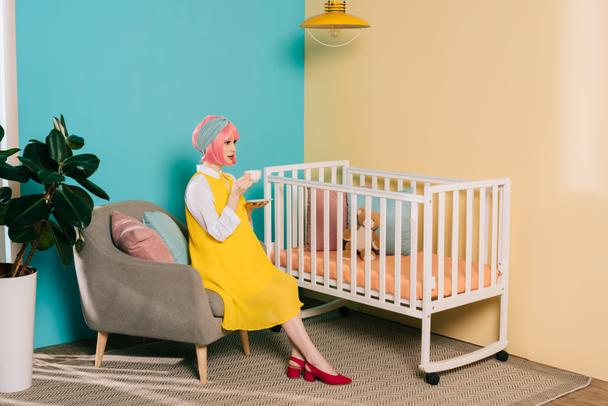 side view of retro styled pregnant pin up woman sitting near baby cot with cup of tea in child room - Photo, Image