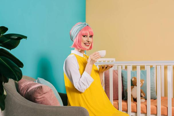 smiling pregnant pin up woman with pink hair sitting near baby cot with cup of tea - Photo, Image