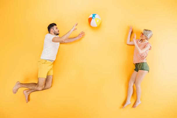 happy young couple playing with beach ball on yellow - Photo, Image