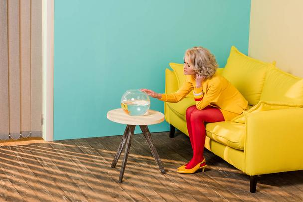 woman in bright retro clothing looking at aquarium fish while resting on sofa at colorful apartment, doll house concept - Photo, Image