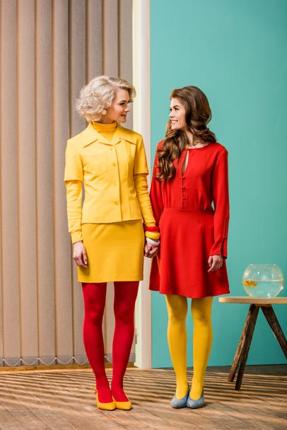 women in bright retro styled clothing holding hands at colorful apartment, doll house concept - Photo, Image