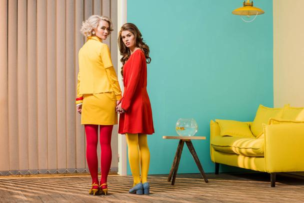rear view of women in bright retro styled clothing holding hands at colorful apartment, doll house concept - Photo, Image
