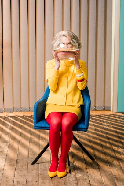 obscured view of woman in retro clothing holding golden fish in aquarium at colorful apartment, doll house concept - Photo, Image