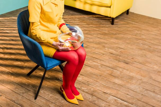 partial view of woman in retro clothing with golden fish in aquarium sitting on chair at colorful apartment, doll house concept - Photo, Image