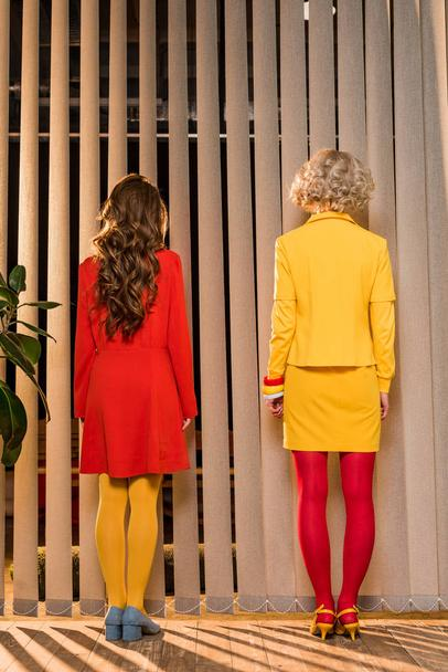 rear view of women in bright clothing standing at window at colorful apartment, doll house concept - Photo, Image