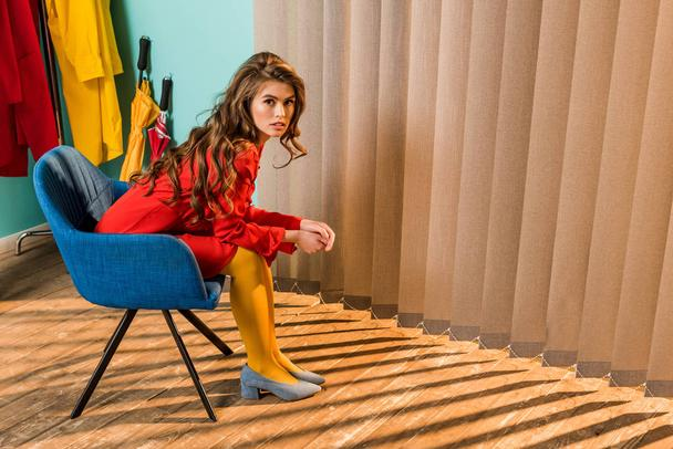 side view of retro styled woman sitting on chair at bright apartment, doll house concept - Photo, Image