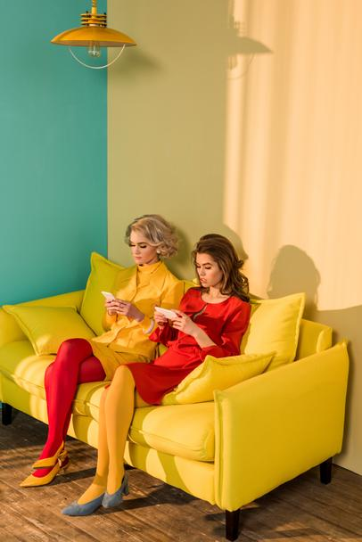 retro styled women using smartphones while resting on yellow sofa, doll house concept - Photo, Image