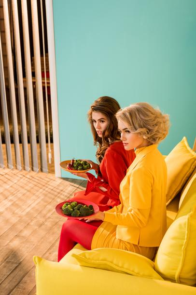pretty women in retro clothing with vegetables on plates sitting on yellow sofa at colorful room, doll house concept - Photo, Image