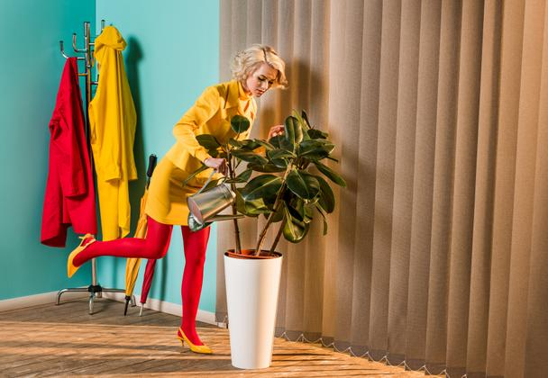 stylish attractive woman in colorful dress watering plant with watering can at home - Photo, Image