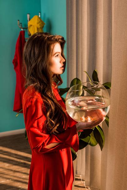 side view of stylish woman in red dress holding aquarium with gold fish and looking away at home - Photo, Image
