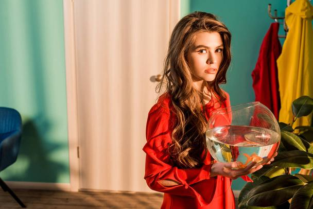 stylish woman in red dress holding aquarium with gold fish and looking at camera at home - Photo, Image