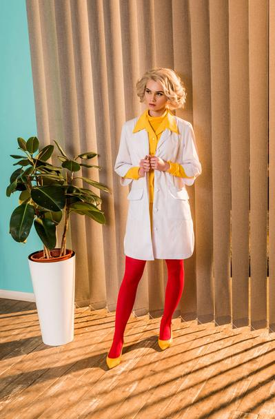 beautiful retro styled doctor posing in colorful dress and white coat in clinic - Photo, Image