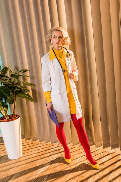 beautiful retro styled doctor in colorful dress standing with clipboard in clinic - Photo, Image