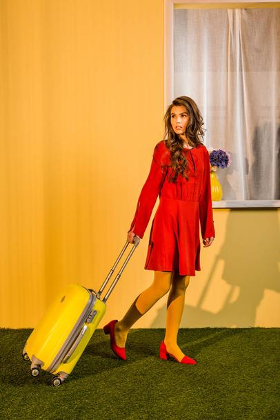 beautiful retro styled woman in red dress walking with suitcase at home, travel concept - Photo, Image