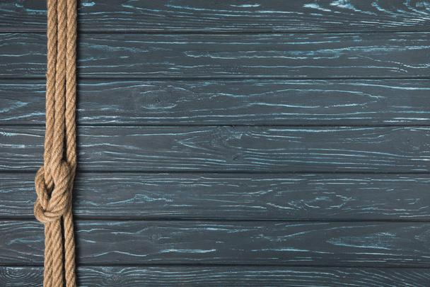 top view of background with brown nautical rope with knot on wooden planks - Photo, Image