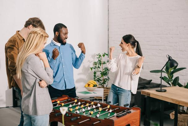 two business colleagues celebrating victory in table football in front of losing coworkers  - Photo, Image