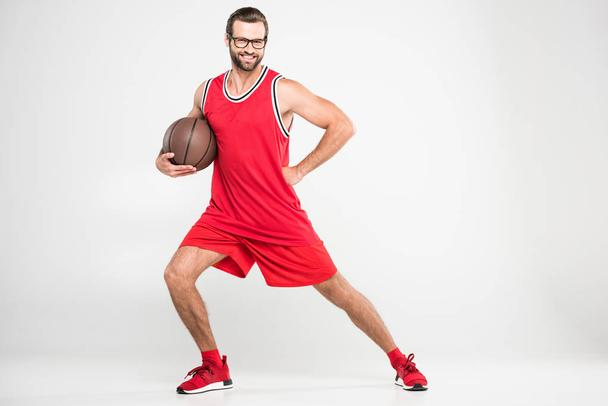 smiling basketball player in red sportswear and retro glasses posing with ball, isolated on white - Photo, Image