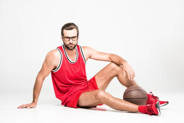 basketball player in red sportswear and eyeglasses sitting with ball, isolated on white - Photo, Image