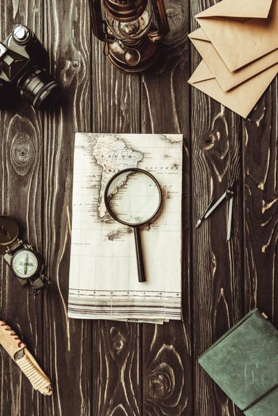 flat lay with arrangement of map, magnifying glass, envelopes, retro photo camera and notebook on dark tabletop - Photo, Image