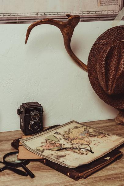 close up view of table with map, eyeglasses, magnifying glasses, retro photo camera and decorative horns - Photo, Image