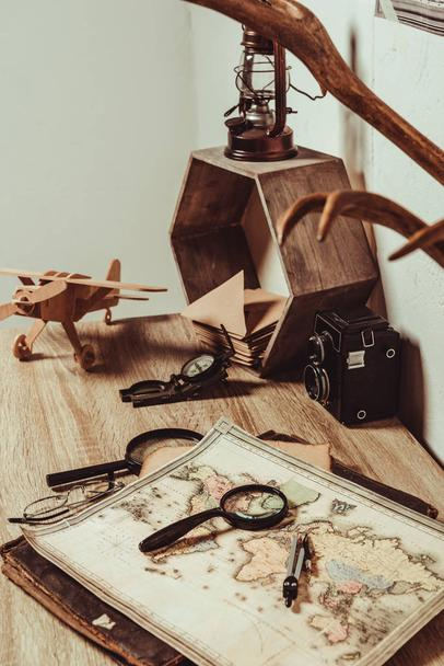 close up view of table with map, magnifying glasses and retro photo camera - Photo, Image