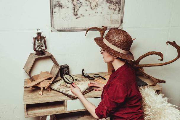 retro style woman in hat with magnifying glass sitting at table with map - Photo, Image