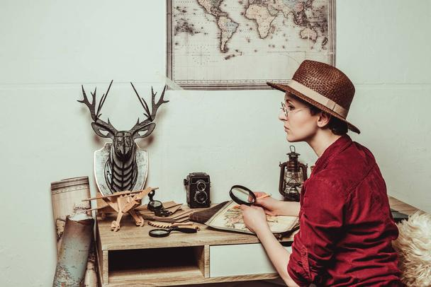 pensive retro style woman in hat with magnifying glass sitting at table with map - Photo, Image