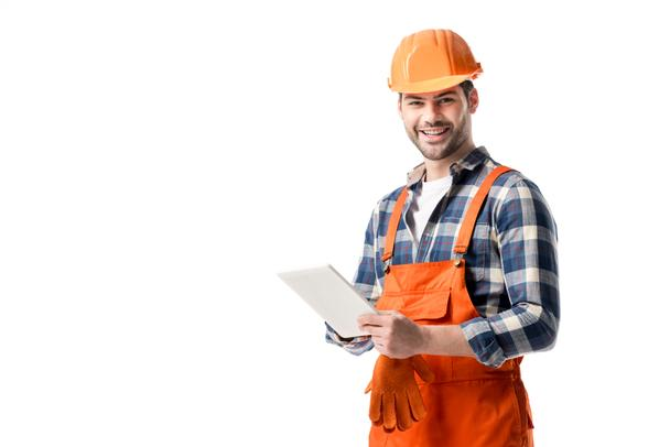 Smiling builder in orange overall and hard hat using digital tablet isolated on white - Photo, Image