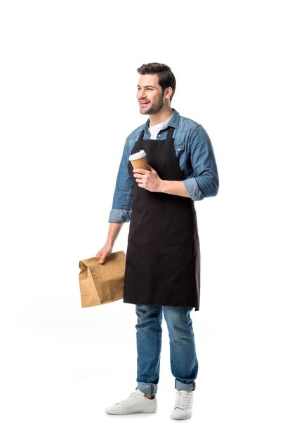 smiling waiter in apron with order to go in hands isolated on white - Photo, Image