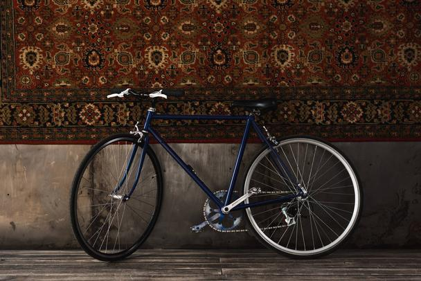vintage road bike indoors in front of rug hanging on wall - Photo, Image