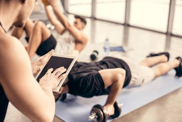 trainer using tablet and counting results of sportsman doing push ups on dumbbells in gym - Photo, Image