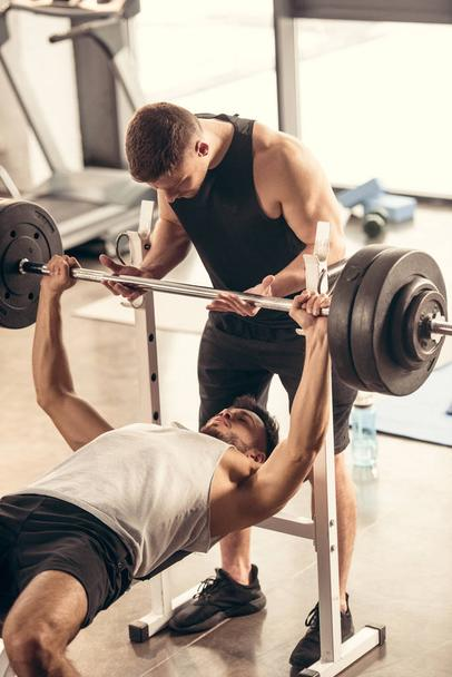 muscular trainer helping sportsman lifting barbell with heavy weights in gym - Photo, Image