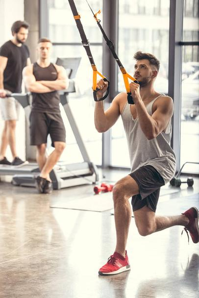 athletic young man training with resistance bands in sports center  - Photo, Image