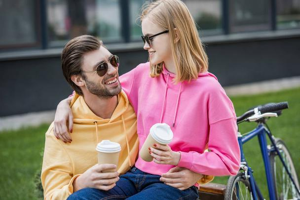 smiling stylish couple in sunglasses sitting on bench with papers cups of coffee  - Photo, Image