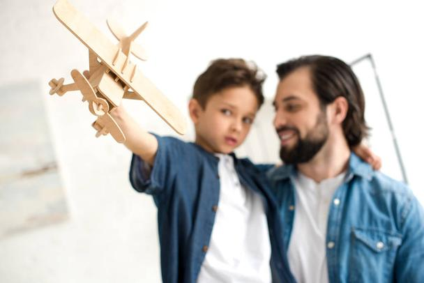 close-up view of father and son playing with wooden toy plane - Photo, Image