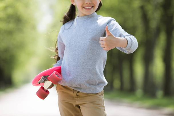 cropped image of child with penny board doing thumb up gesture - Photo, Image
