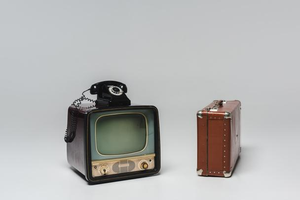 vintage tv with rotary phone and suitcase on grey - Photo, Image