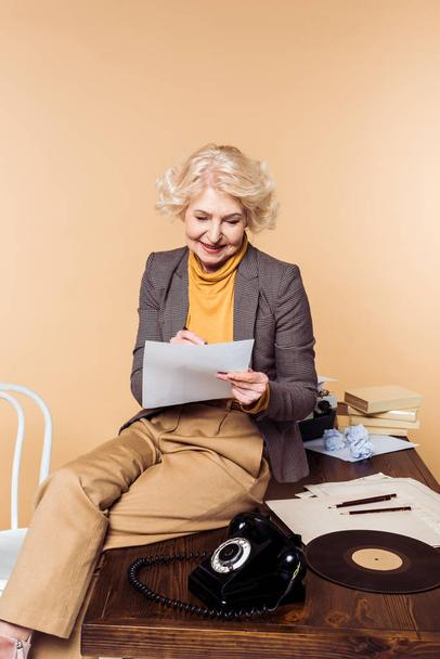 stylish senior woman writing in paper and sitting on table with rotary phone and vinyl disc - Photo, Image