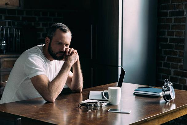 depressed young man sitting on kitchen with laptop and looking away - Photo, Image