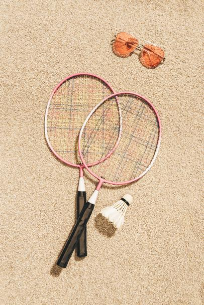 top view of arranged badminton equipment and sunglasses on sand - Photo, Image