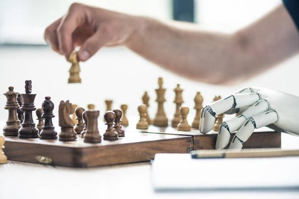 close-up view of person and robotic arm playing chess - Photo, Image